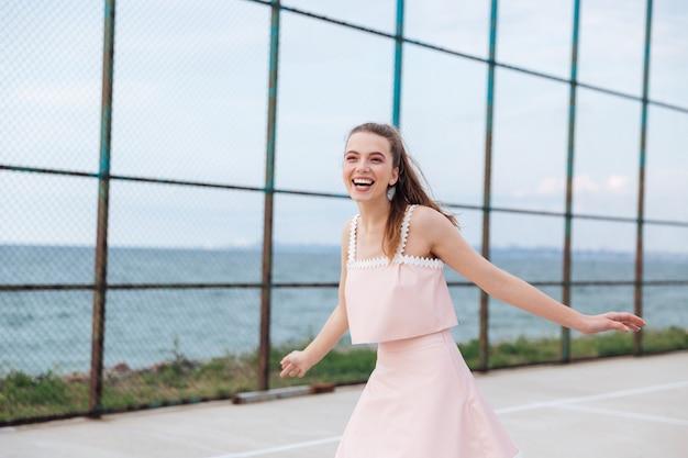笑って、屋外で楽しんでいる陽気な魅力的な若い女性