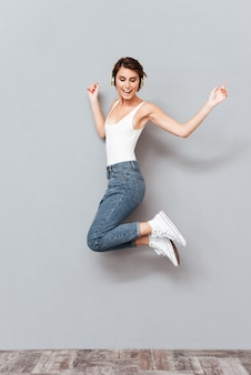 Веселая привлекательная молодая женщина слушает музыку в наушниках и прыгает в воздухе на сером фоне