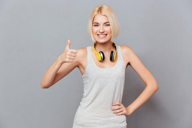 Веселая привлекательная молодая женщина показывает палец вверх над серой стеной