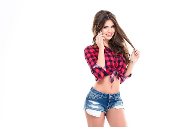 Cheerful attractive young woman standing and talking on mobile phone over white wall
