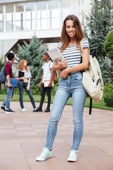 Веселая привлекательная молодая женщина-студент с рюкзаком стоит и улыбается в кампусе