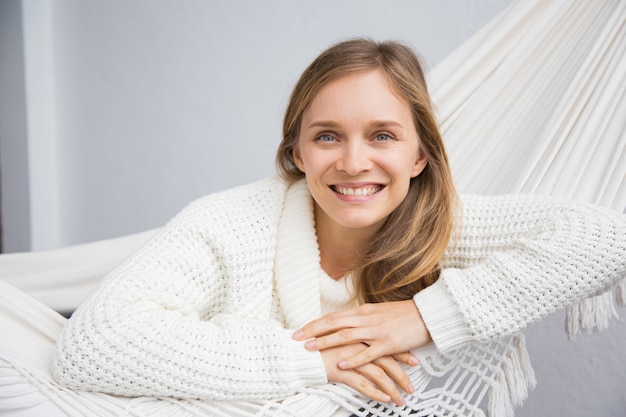 Cheerful attractive young woman in white sweater relaxing
