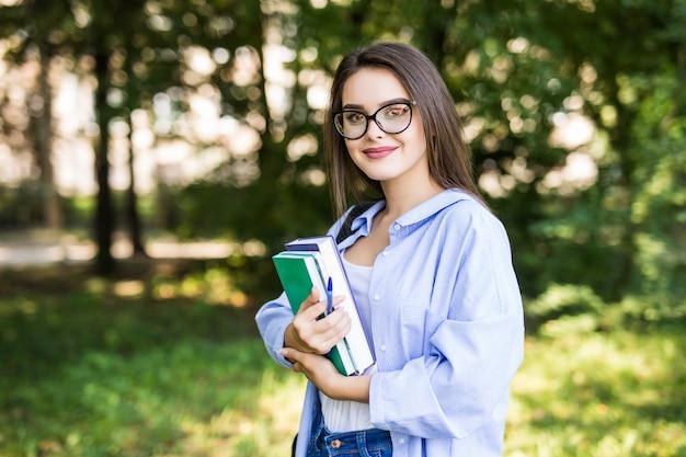 立っていると公園で笑顔の本を持つ陽気な魅力的な若い女性