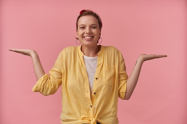 Cheerful attractive young woman in yellow shirt with headband on head looks happy and holding copyspace on two palms over pink wall