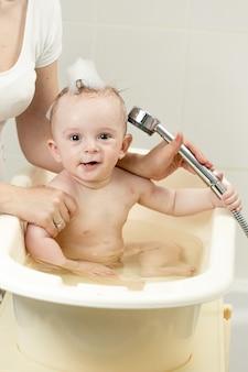 목욕을 하고 샤워 헤드를 가지고 노는 쾌활한 아기