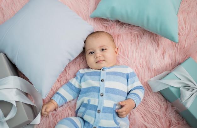 베개와 선물 모피 담요에 누워 쾌활한 아기