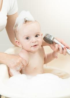 욕조에서 샤워 헤드를 가지고 노는 쾌활한 아기