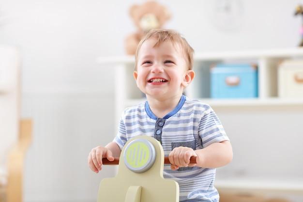 Веселый мальчик качается на качалке в форме самоката