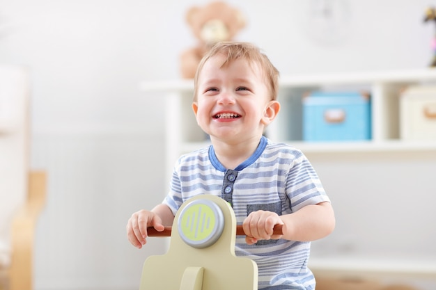 Cheerful baby boy swinging on a rocking chair in the shape of a scooter