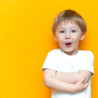Cheerful baby boy three years old in white t-shirt stands