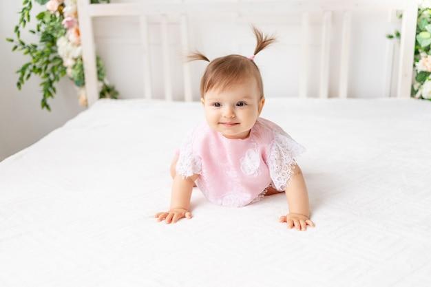 Веселая девочка сидит в яркой красивой комнате на белой кровати в кружевном боди и улыбается