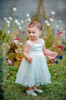 Веселая девочка с длинным белым платьем стоит на траве в саду и улыбается