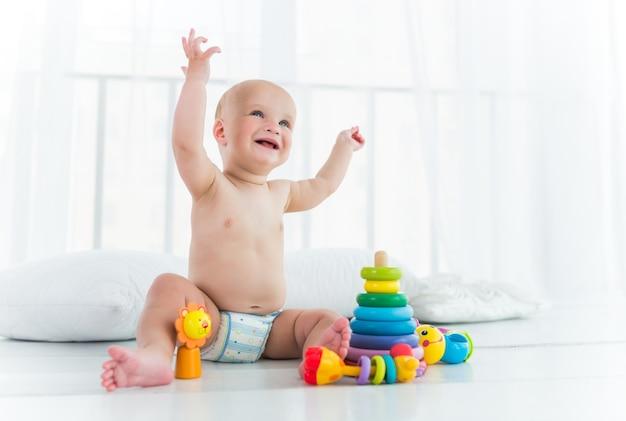 Веселый малыш в пеленке смеется и играет