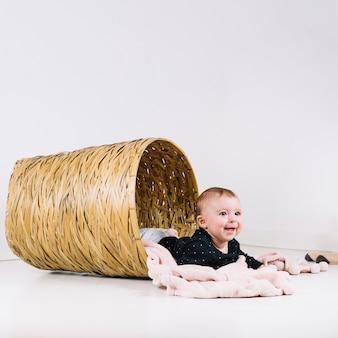 Cheerful baby lying in basket