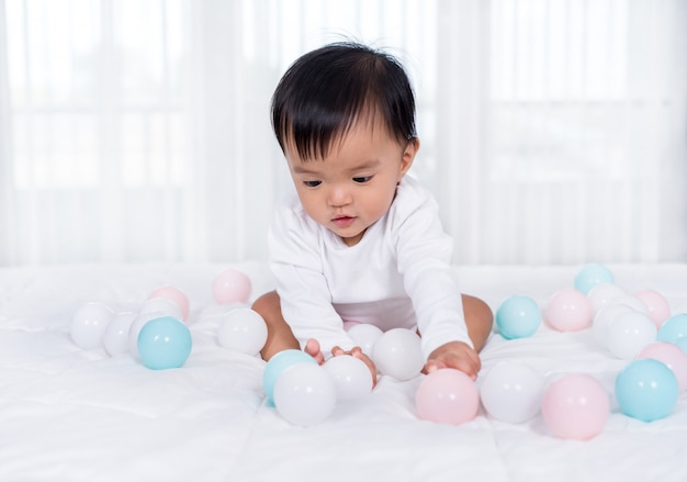 Cheerful baby playing color ball on bed