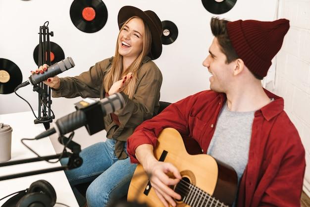 Веселая группа молодых музыкантов играет свою песню в радиорубке, радиопередача