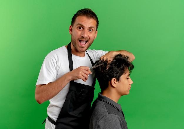 Uomo allegro del barbiere in grembiule che taglia i capelli con le forbici del cliente soddisfatto che sta sopra la parete verde