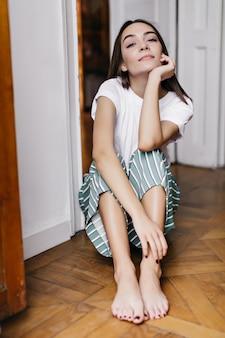 Allegra donna a piedi nudi in pigiama in posa con l'espressione del viso interessato. foto dell'interno del modello femminile europeo rilassato che si siede sul pavimento e che osserva.