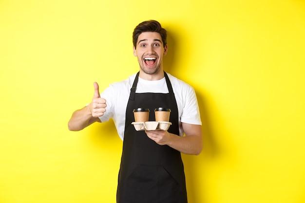 Веселый бариста рекомендует свое кафе, держа кофейные чашки на вынос и показывая большие пальцы руки вверх, стоя у желтой стены