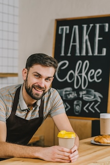 Cheerful barista with hot drink