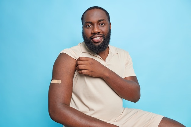 L'uomo adulto barbuto allegro viene vaccinato secondo il programma in clinica mostra il braccio con cerotto adesivo seduto contro il muro blu