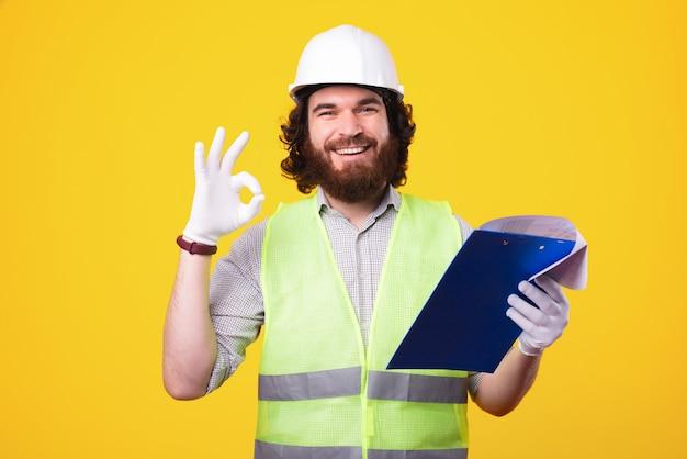헬멧을 착용하고 종이 작업을 보면서 확인 제스처를 보여주는 쾌활한 수염 건축가 남자