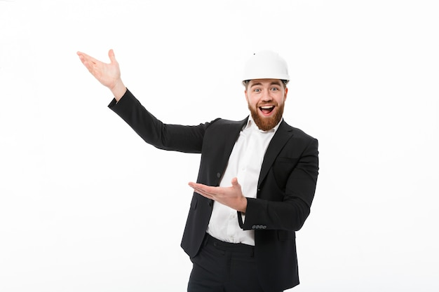 Cheerful bearded business man in protective helmet pointing away