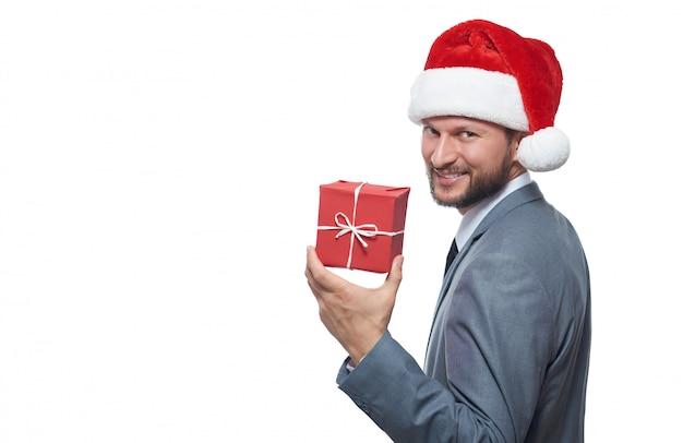 Веселый бородатый бизнесмен в шляпе рождество, улыбаясь через плечо, сохраняя небольшой рождественский подарок.