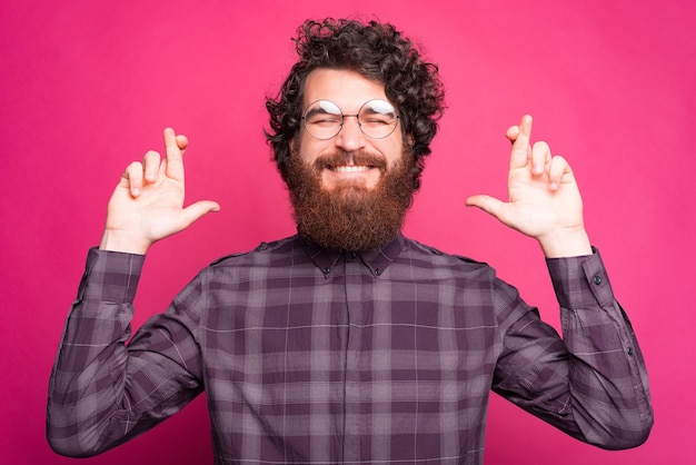 指を交差させ、大きな夢を夢見ている陽気なひげを生やした白人男性