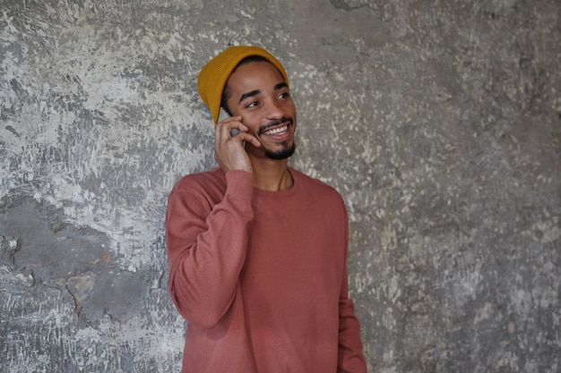 Cheerful bearded dark skinned male with charming brown eyes looking aside and smiling happily while having nice talk on phone