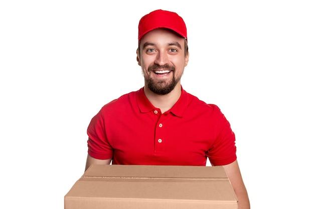Веселый бородатый курьер в красной форме и кепке смотрит с дружелюбной улыбкой, неся большую картонную коробку