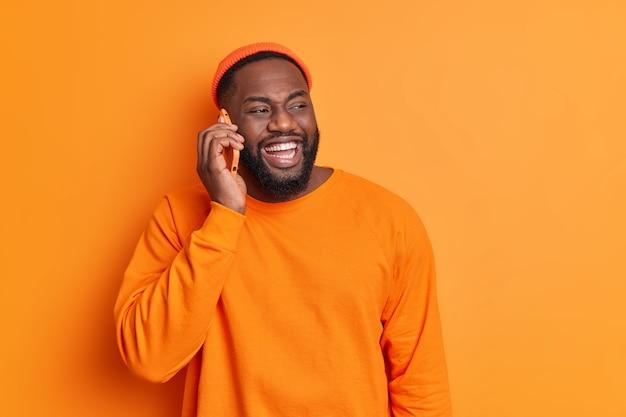 쾌활한 수염을 가진 남자는 전화로 미소를 지으며 주황색 스웨터를 입은 하얀 이빨을 가지고 있고 모자는 옆으로 외모가 주말 계획을 행복하게 논의합니다.