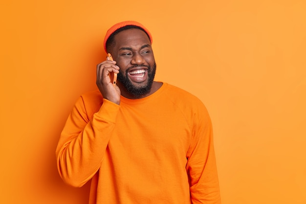 Cheerful bearded guy makes phone call smiles broadly has white teeth dressed in orange sweater and hat looks aside happily discusses plans for weekends