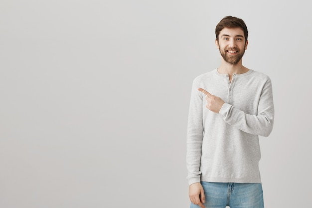Cheerful bearded guy pointing left at advertisement