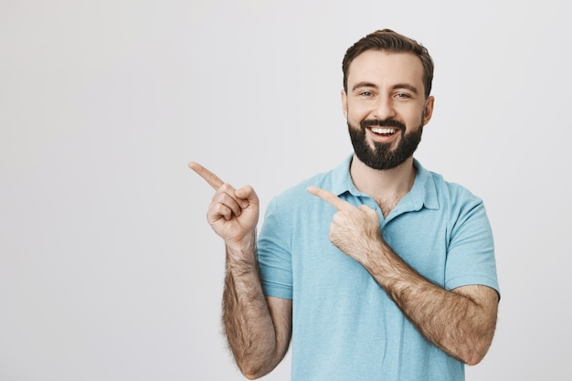 Cheerful bearded guy pointing upper left corner