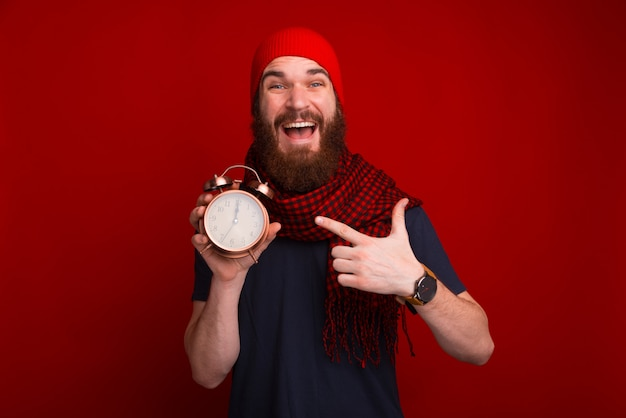 Cheerful bearded guy pointing at vintage clock and showing this at camera, over red space