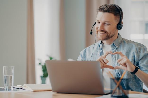 Веселый бородатый красивый парень в повседневной одежде сидит перед экраном ноутбука за столом и болтает онлайн с подругой, показывая пальцами форму сердца. образ жизни, концепция видеоконференцсвязи