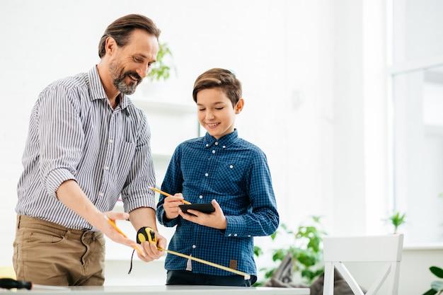 笑顔の息子とテーブルの横に立って、黄色の巻尺を使用して陽気なひげを生やしたハンサムな男
