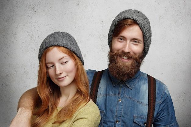 Веселый бородатый хипстер в джинсовой рубашке смеется, обнимая свою красивую рыжую подругу, которая смотрит на него с хитрой загадочной улыбкой.
