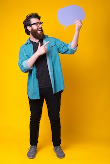 Cheerful bearded hipster is holding a violet speech bubble standing in full body