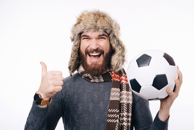 Cheerful bearded hipster man holding soccer ball and showing thumbs up