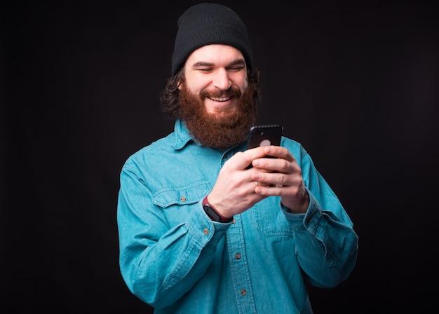暗い壁の上で彼のスマートフォンを使用して陽気なひげを生やしたヒップスターの男