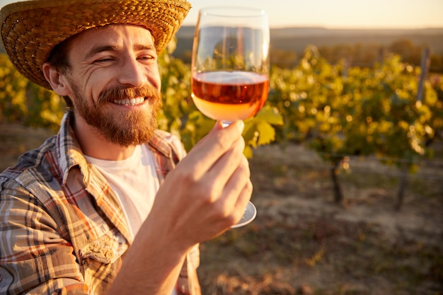 Cheerful bearded male farmer tasting rose wine from glass while standing near grape trees in vineyard