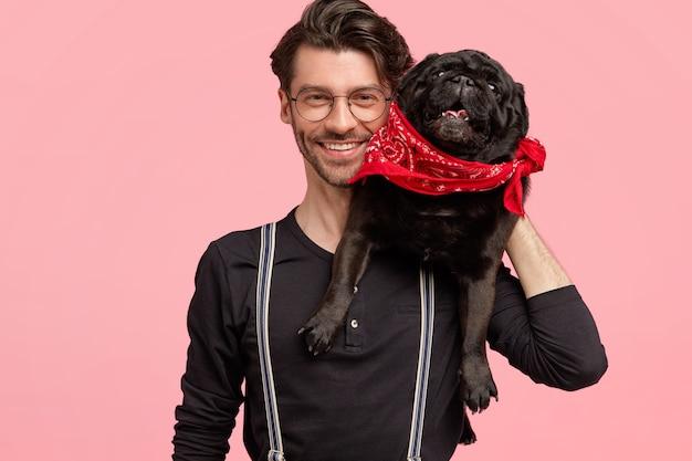 쾌활한 수염 난 남성은 이빨 미소를 가지고 있으며 혈통 개와 함께 포즈를 취하고 애완 동물을 좋아하며 세련된 검은 셔츠와 멜빵을 입고 분홍색 벽 위에 절연되어 있습니다. 동물과 함께 행복 한 사람