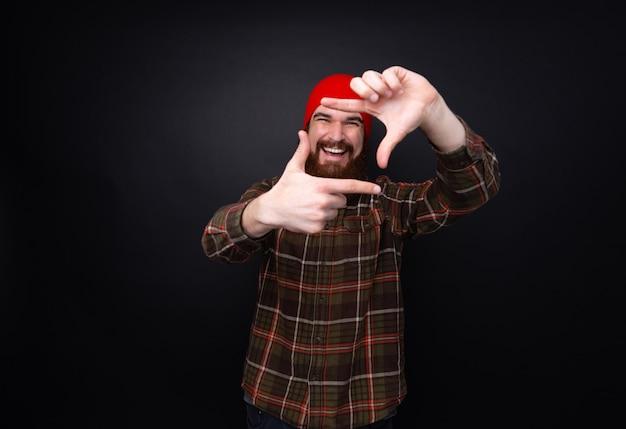 Веселый бородатый мужчина делает кадр с пальцами над темной