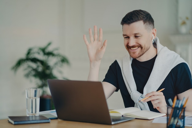 Cheerful bearded man has video conference online waves palm in laptop computer uses wireless earphones poses at coworking space dressed casually writes down information in diary smiles gladfully