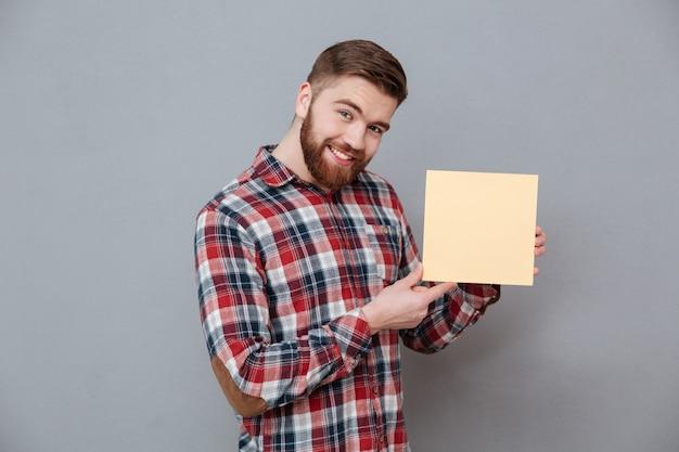 Uomo barbuto allegro che tiene carta in bianco