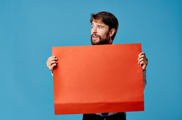 Cheerful bearded man holding red banner blue background studio