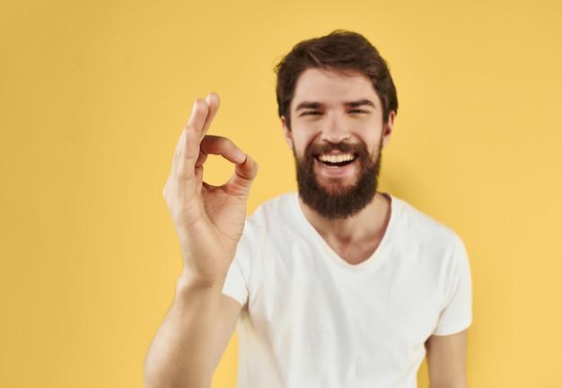 彼の手黄色の背景で身振りで示す白いtシャツの陽気なひげを生やした男。高品質の写真