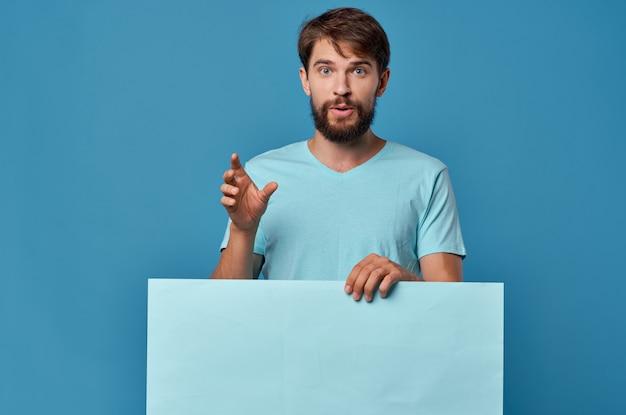 青いtシャツモックアップポスタースタジオ孤立した背景の陽気なひげを生やした男